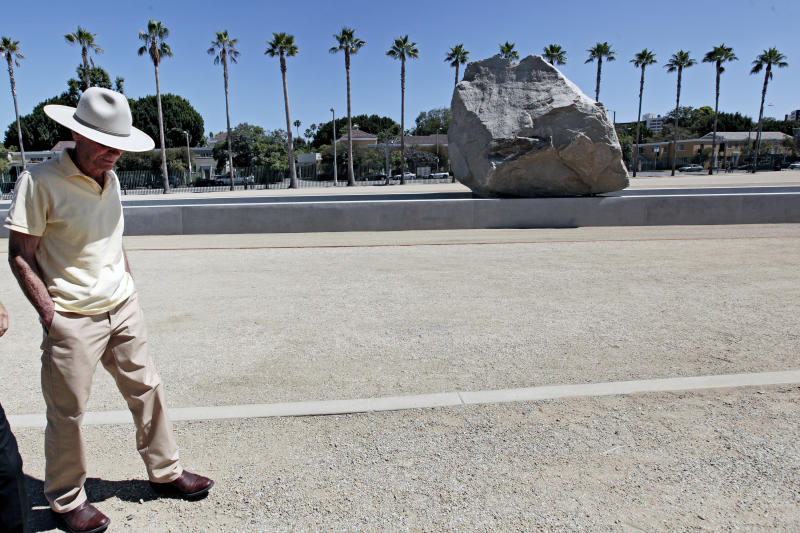 "Artist Michael Heizer walks past his sculpture ""Levitated Mass"" prior to a dedication ceremony featuring a 340-ton granite boulder sitting above a 456-foot-long concrete slot at the Los Angeles County Museum of Art in Los Angeles, on Sunday June 24, 2012. Thousands showed up under sunny skies as the gigantic work titled ""Levitated Mass"" was unveiled Sunday on the museum's rear lawn, where it is intended to remain forever. (AP Photo/Richard Vogel)"