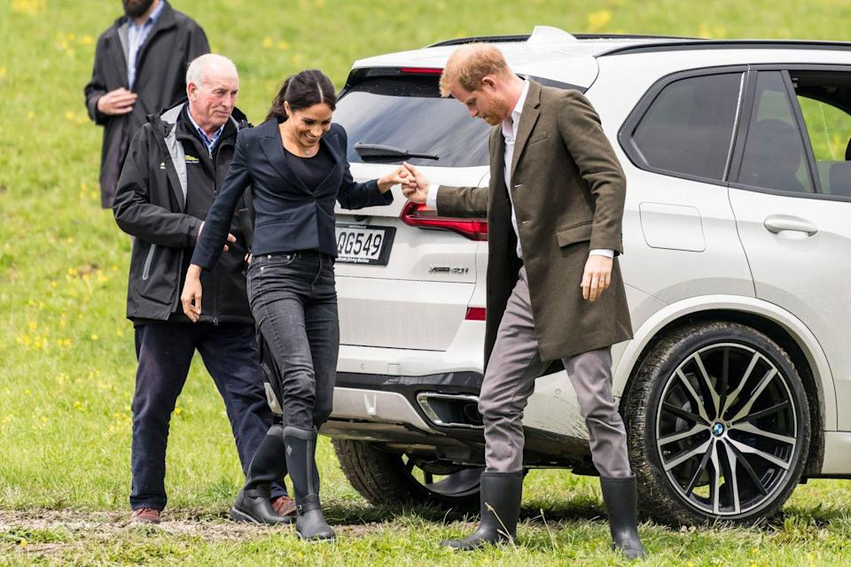 """<p>Prince Harry offered a helping hand to his pregnant wife as she navigated the muddy grass of The North Shore Riding Club in Auckland, where the couple made a visit to join<a href=""""https://www.elle.com/uk/life-and-culture/a24423487/meghan-markle-prince-harry-welly-wanging/"""" rel=""""nofollow noopener"""" target=""""_blank"""" data-ylk=""""slk:in a welly waning competition."""" class=""""link rapid-noclick-resp""""> in a welly waning competition. </a></p>"""
