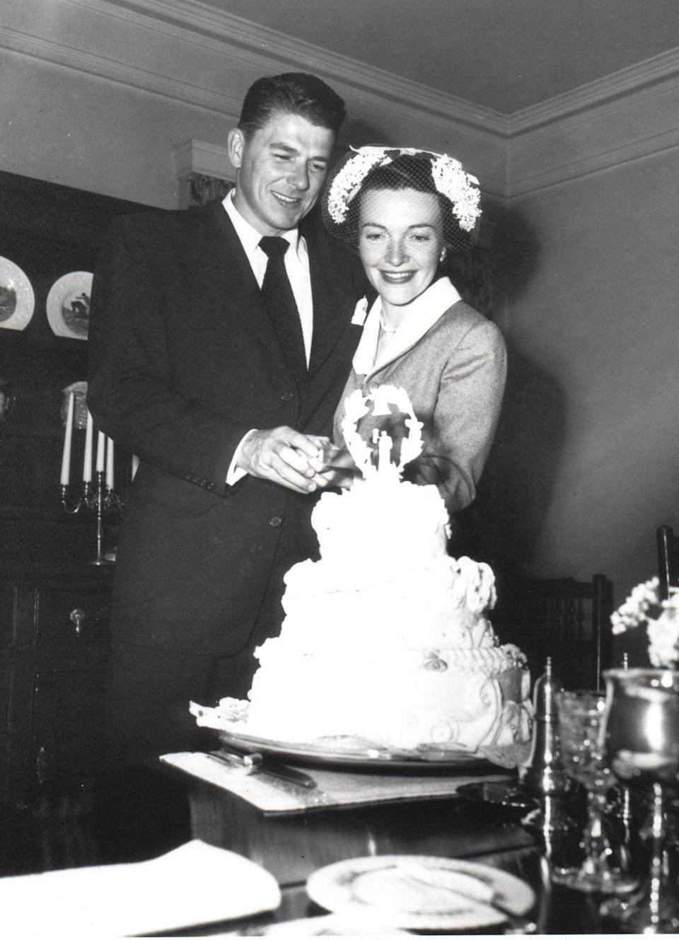<p>At their wedding, a young Ronald and Nancy Reagan cut their cake. </p>