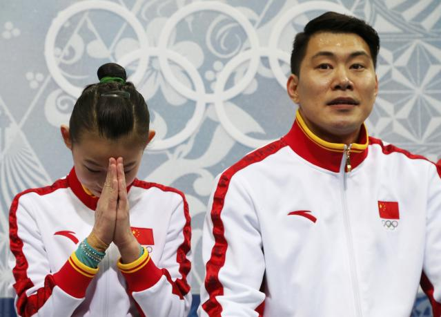 """China's Cheng Peng and Hao Zhang react in the """"kiss and cry"""" area during the Figure Skating Pairs Short Program at the Sochi 2014 Winter Olympics, February 11, 2014. REUTERS/Lucy Nicholson (RUSSIA - Tags: OLYMPICS SPORT FIGURE SKATING)"""