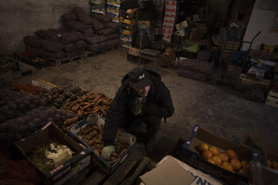 """FILE - In this Sunday, March 16, 2014 file photo a Tatar man works in a fruit warehouse within a market in Bakhchisaray, Crimea. Despite the pebble beaches and cliff-hanging castles that made Crimea famous as a Soviet resort hub, the Black Sea peninsula has long been a corruption-riddled backwater in economic terms. The Kremlin, which decided to take the region from Ukraine after its residents voted in a referendum to join Russia, has begun calculating exactly what it will cost to support Crimea's shambolic economy, which one Russian minister described as """"no better than Palestine."""" (AP Photo/Manu Brabo, File)"""