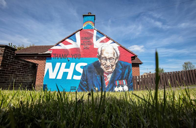 TOPSHOT - A street art graffiti mural, showing the logo of the NHS (National Health Service), and an image 100-year-old veteran Captain Tom Moore who raised over GBP 30 million for NHS charities, is pictured in east Belfast on May 5, 2020. - The number of people killed by the coronavirus in the UK stands at 32,313, according to official figures on May 5 2020, the second highest death toll in the world. Figures from the Office for National Statistics showed Britain had now overtaken Italy, which has reported 29,029 fatalities, and now only stands behind the US with 68,700 deaths, the largest single-country toll. (Photo by Paul Faith / AFP) (Photo by PAUL FAITH/AFP via Getty Images)