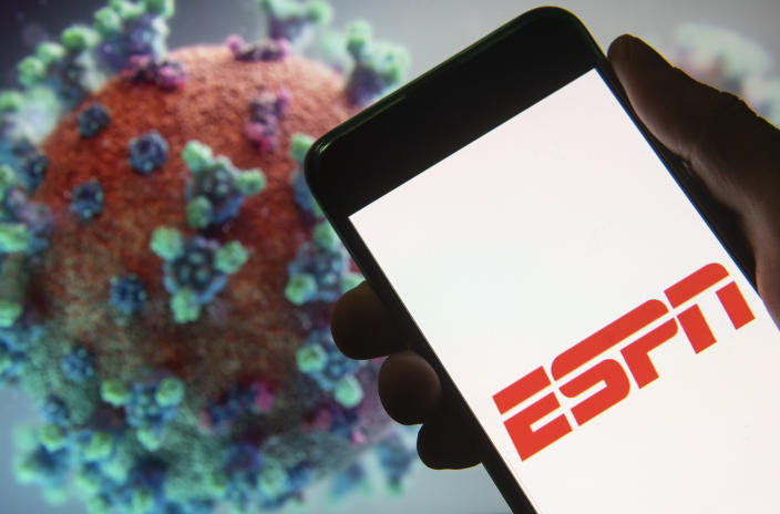CHINA - 2020/03/18: In this photo illustration the American sports television channel ESPN logo seen displayed on a smartphone with a computer model of the COVID-19 coronavirus on the background. (Photo Illustration by Budrul Chukrut/SOPA Images/LightRocket via Getty Images)