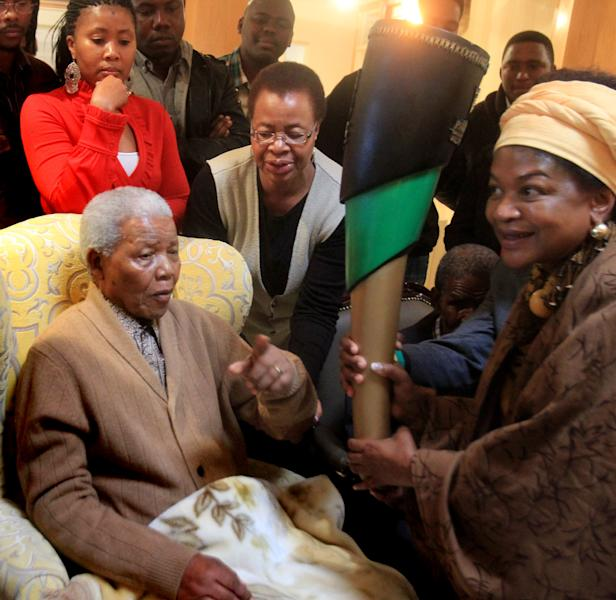 FILE - In this Wednesday, May 30, 2012 file photo, South Africa's former President Nelson Mandela, left, receives a torch to celebrate the African National Congress' centenary from ANC chairperson Baleka Mbete, right, in Mandela's home village of Qunu in rural eastern South Africa. Mandela's wife Graca is at center. The emotional pain and practical demands facing Mandela's family are universal: confronting the final days of an elderly loved one. There are no rules for how or when the end may arrive. Some choose to let go with little medical interference; others seek aggressive medical care. Mandela's status as a respected global figure only complicates the situation, doctors and end-of-life experts say. (AP Photo/Lulamile Feni-Daily Dispatch, Lulamile Feni, File)