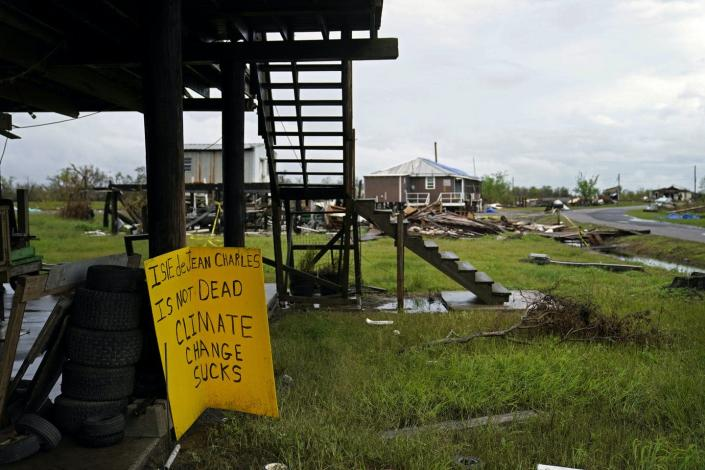 Severely damaged homes and a sign that reads: 'Isle de Jean Charles is not dead. Climate change sucks.'