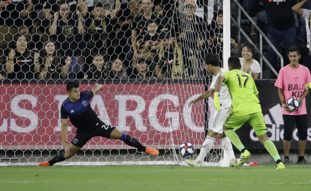 Los Angeles FC forward Carlos Vela, center, scores past San Jose Earthquakes goalkeeper Daniel Vega (17) and defender Nick Lima during the first half of an MLS soccer match Wednesday, Aug. 21, 2019, in Los Angeles. (AP Photo/Marcio Jose Sanchez)