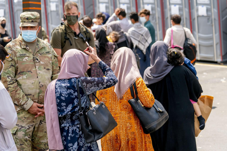 People evacuated from Afghanistan step off a bus as they arrive at a processing center in Chantilly, Monday, Aug. 23, 2021, after arriving on a flight at Dulles International Airport. (AP Photo/Andrew Harnik)