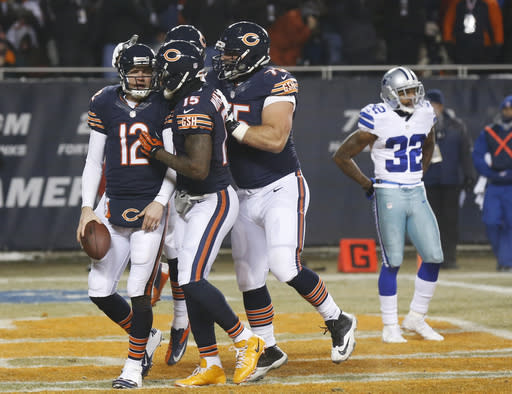 Chicago Bears quarterback Josh McCown (12) celebrates his touchdown run with wide receiver Brandon Marshall (15) and offensive guard Kyle Long (75) during the first half of an NFL football game against the Dallas Cowboys, Monday, Dec. 9, 2013, in Chicago. At right is Cowboys cornerback Orlando Scandrick (32). (AP Photo/Charles Rex Arbogast)