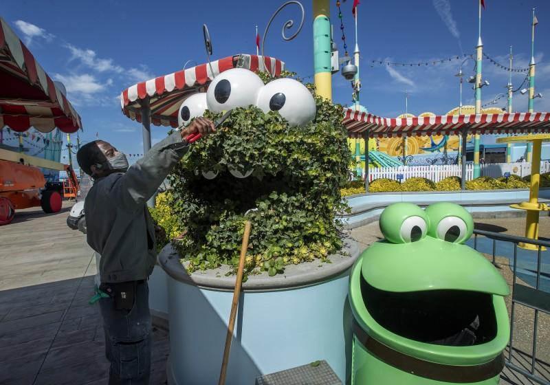 UNIVERSAL CITY, CA - MARCH 17, 2021: Horticulturist Frank Phillips trims English ivy around a decorative caterpillar located at Super Silly Fun Land on the grounds of Universal Studios Hollywood as the theme park prepares to re-open. (Mel Melcon / Los Angeles Times)