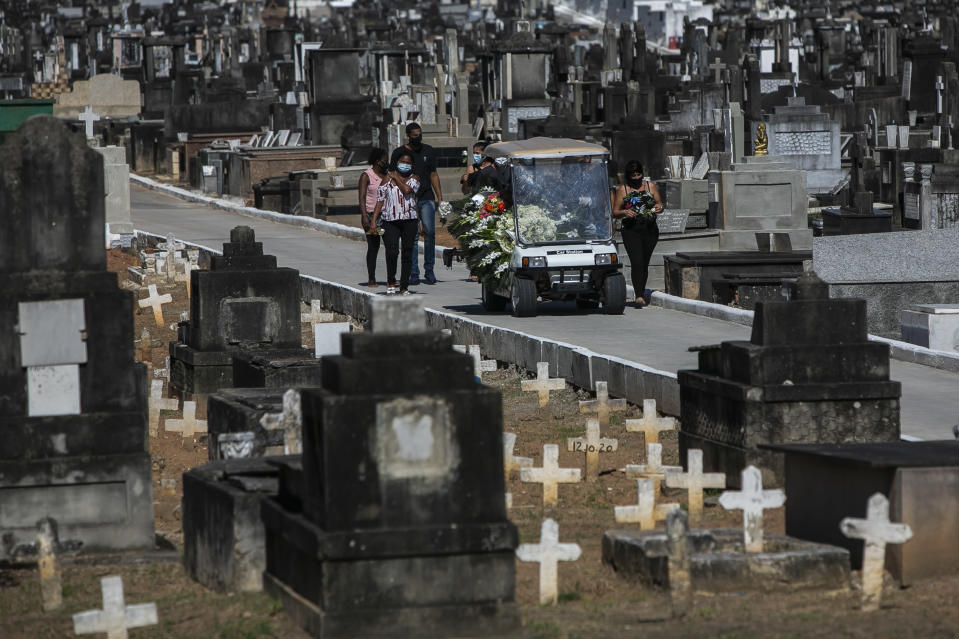 FILE - In this Jan. 7, 2021 file photo relatives attend the burial of 71-year-old Jose Abelardo Bezerra, who died from COVID-19 related complications, at the Inhauma cemetery in Rio de Janeiro, Brazil. Brazil has suffered more than 200,000 COVID-19 deaths, the second-highest total in the world after the United States, with infections and deaths surging again. (AP Photo/Bruna Prado, File)