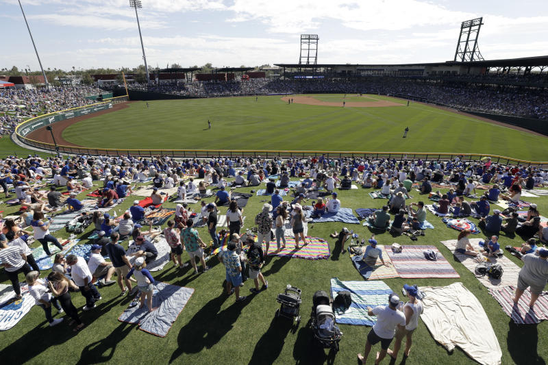Fans watch the Chicago Cubs play the Milwaukee Brewers during a spring training baseball game Saturday, Feb. 29, 2020, in Mesa, Ariz. (AP Photo/Gregory Bull)