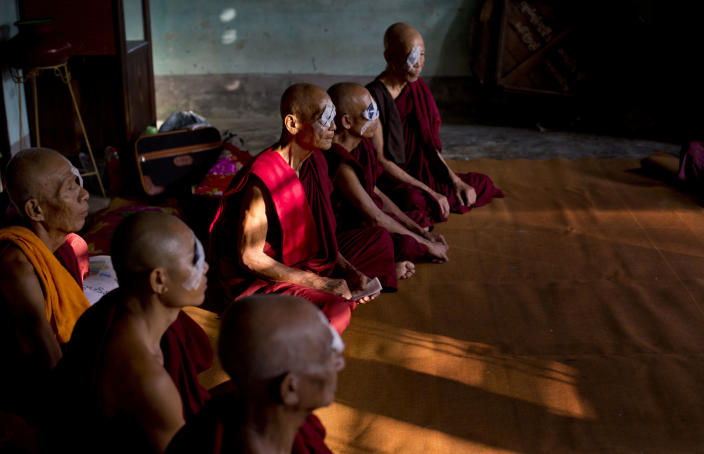 """In this Oct. 23, 2013 photo, Buddhist monks with eye patches and bandages rest on the floor of a Buddhist shrine following simple operations to remove cataracts in Bago, Myanmar. Five decades of isolation, military rule and woeful health care have left Myanmar with one of the highest rates of blindness in the region. Now the veil of darkness is starting to lift, thanks to an """"assembly line"""" surgical procedure that allows cataracts to be removed safely, without stitches, through two small incisions. (AP Photo/ Gemunu Amarasinghe)"""