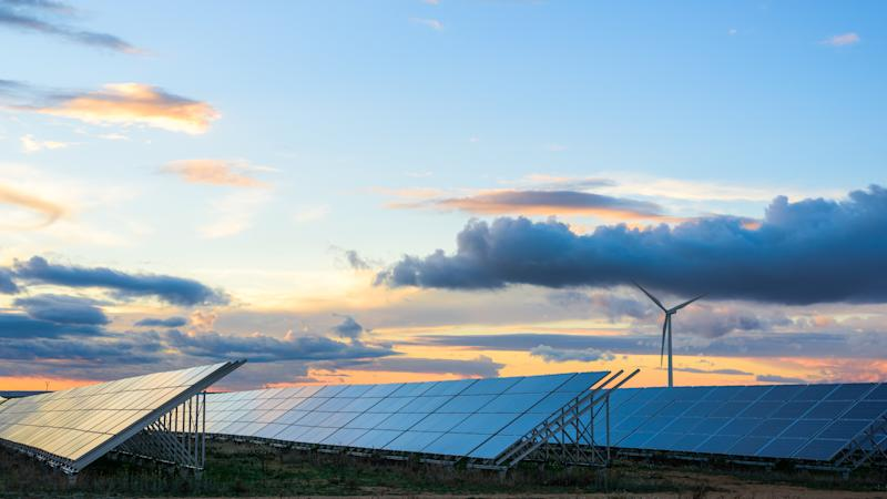 Solar panels and a wind turbine with the sun setting in the background.