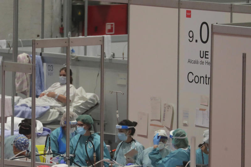 CAPTION CORRECTS THE DATE - In this photo taken on Thursday, April 2, 2020, doctors work at a temporary field hospital set in Ifema convention and exhibition in Madrid, Spain. Most of the 1,850 patients brought to the Ifema field hospital are not in serious conditions. In fact, 800 had been discharged by Thursday, although six had died since doors opened 12 days ago. The new coronavirus causes mild or moderate symptoms for most people, but for some, especially older adults and people with existing health problems, it can cause more severe illness or death. (AP Photo/Manu Fernandez)