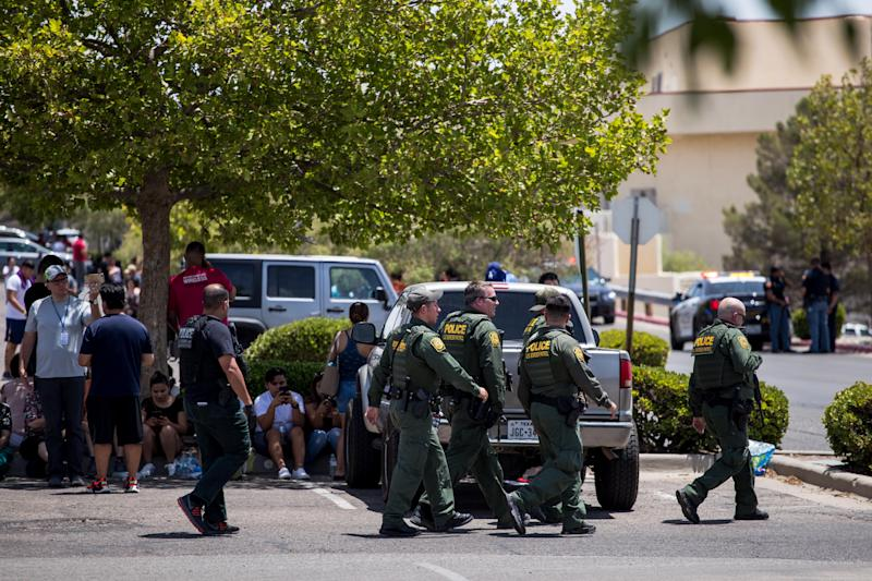 Customs and Border Patrol police walk past individuals that were evacuated from Cielo Vista Mall and a Wal-Mart where a mass shooting occurred in El Paso, Texas, Saturday
