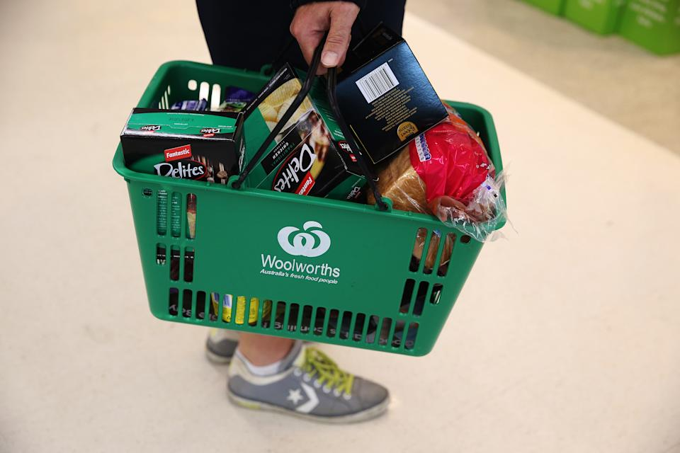Photo shows Woolworths carrying a basket of groceries.