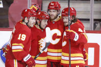 Calgary Flames' Johnny Gaudreau, second from left, celebrates his goal against the Edmonton Oilers with teammates Matthew Tkachuk, Noah Hanifin and Rasmus Andersson, from left, during the second period of an NHL hockey game Saturday, April 10, 2021, in Calgary, Alberta. (Larry MacDougal/The Canadian Press via AP)