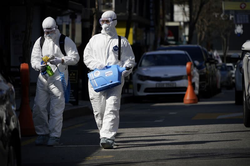 Employees from a disinfection service company sanitize a shopping district in Seoul