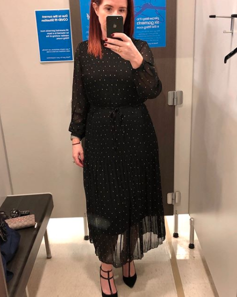 Woman in Kmart's dressing rooms trying on a long-sleeved polka dot dress
