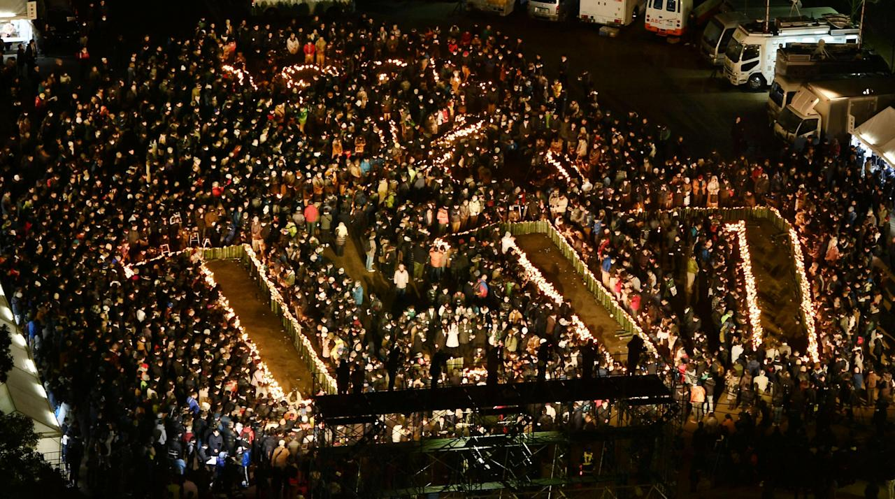 People gather around candles forming characters commemorating the 22nd anniversary of the Great Hanshin earthquake at a park in Kobe, Hyogo prefecture, in this photo taken by Kyodo January 17, 2017. Mandatory credit Kyodo/via REUTERS ATTENTION EDITORS - THIS IMAGE WAS PROVIDED BY A THIRD PARTY. EDITORIAL USE ONLY. MANDATORY CREDIT. JAPAN OUT. NO COMMERCIAL OR EDITORIAL SALES IN JAPAN.
