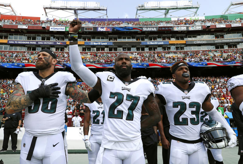 Standing between teammates Chris Long and Rodney McLeod, Eagles safety Malcolm Jenkins (27) raised his fist during the national anthem. (AP)