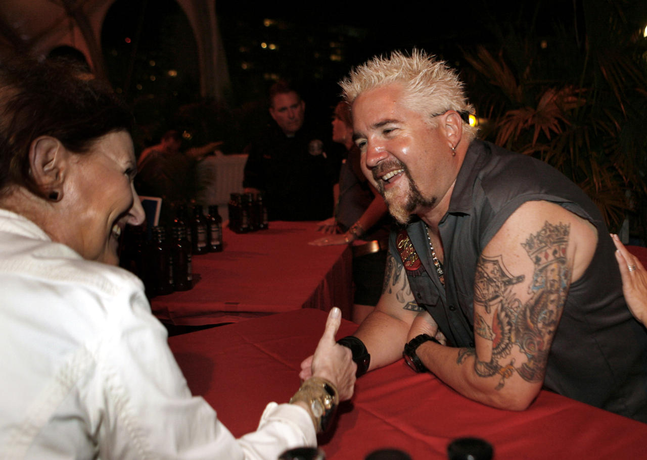 Food network personality Guy Fieri greets fans while competing in the Burger Bash at the Food Network South Beach Wine & Food Festival in Miami Beach, Fla., Friday, Feb. 24, 2012. (AP photo/Jeffrey M. Boan)