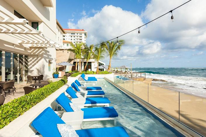 """<p><strong>Best for:</strong> Families looking for a no-passport-required tropical getaway</p> <p>At the historic <a href=""""https://cna.st/affiliate-link/EmXFUGnvfqr4tthF6geGKd54JSqWK29xBKmAxkCn7xub43SAC7gTag5rMRawAX1LXzsrdLCi3eY2Eq5gp9rYaJ?cid=60731f13c549504d1fb958f0"""" rel=""""nofollow noopener"""" target=""""_blank"""" data-ylk=""""slk:Condado Vanderbilt"""" class=""""link rapid-noclick-resp"""">Condado Vanderbilt</a>, butler service will deliver a frozen <a href=""""https://www.cntraveler.com/gallery/caribbean-cocktails-that-are-easy-to-make-at-home?mbid=synd_yahoo_rss"""" rel=""""nofollow noopener"""" target=""""_blank"""" data-ylk=""""slk:piña colada"""" class=""""link rapid-noclick-resp"""">piña colada</a> to the resort's oceanfront pools or white sand beach. (The drink was invented in Old San Juan, after all.) Take in sweeping, palm-tree-lined shore views from a standard room or a spacious one- or two-bedroom suite—all come with scenic views and in-room french press coffee makers stocked with Puerto Rico-grown beans. Former Blue Hill chef Juan Jose Cuevas oversees the resort's restaurants, where he combines his culinary prowess with the flavors and island-grown ingredients of his home town. Don't miss the chef's epic banana bread, made using fruit grown on the island. </p> <p><strong>Book now:</strong> <a href=""""https://cna.st/affiliate-link/Daa4E2BFEqLR6d4JMn9GQ7FXGpZ8m9eByKpX8kNuNHQdoVWzXTMFPEP4DCyDAgzLAY2n7Fn?cid=60731f13c549504d1fb958f0"""" rel=""""nofollow noopener"""" target=""""_blank"""" data-ylk=""""slk:From $389 per night, hotels.com"""" class=""""link rapid-noclick-resp"""">From $389 per night, hotels.com</a></p>"""