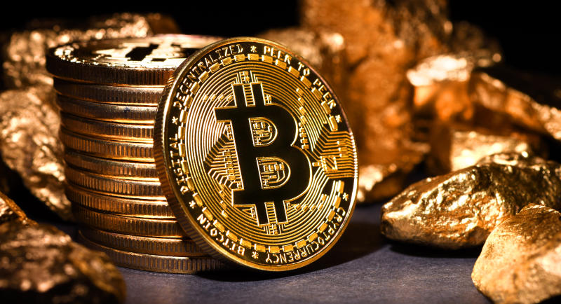 İstanbul, Turkey - February 19, 2018: Close up shot of gold nuggets and bitcoin memorial coins on a desk. Bitcoin is a crypto currency and a worldwide payment system.