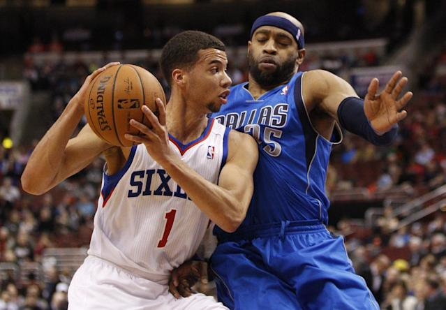 Philadelphia 76ers' Michael Carter-Williams, left, drives to the basket with Dallas Mavericks' Vince Carter, right, defending during the first half of an NBA basketball game, Friday, Feb. 21, 2014, in Philadelphia. (AP Photo/Chris Szagola)