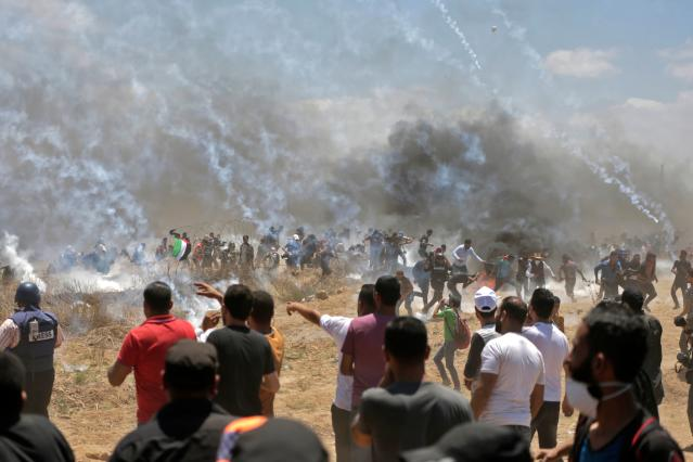 <p>Palestinian protesters run for cover from tear gas during clashes with Israeli forces near the border between the Gaza Strip and Israel east of Gaza City on May 14, 2018, as Palestinians protest the inauguration of the U.S. Embassy following its controversial move to Jerusalem. (Photo: Mahmud Hams/AFP/Getty Images) </p>