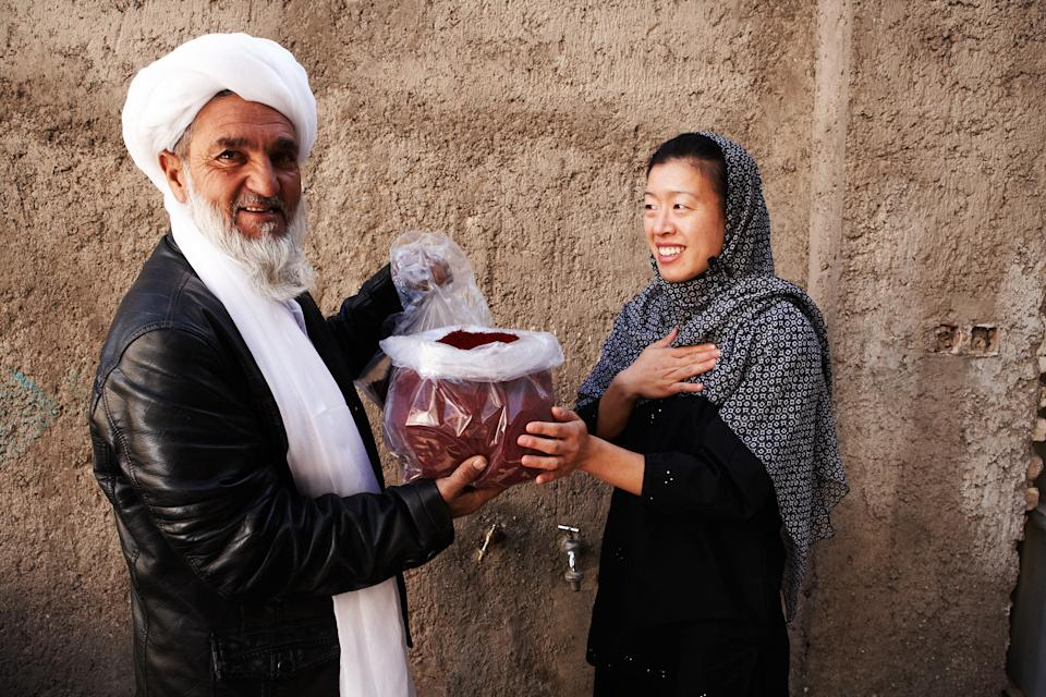 Kim Jung and an Afghan farmer show the saffron that had been farmed there for Rumi Spice.
