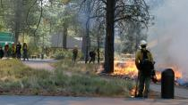 In this May 14, 2021, photo provided by the High Desert Museum, U.S. Forest Service firefighters carry out a prescribed burn on the grounds of the High Desert Museum, near Bend, Oregon. The prescribed burn is part of a massive effort in wildlands across the West to prepare for a fire season that follows the worst one on record. (Kyle Kosma/High Desert Museum via AP)