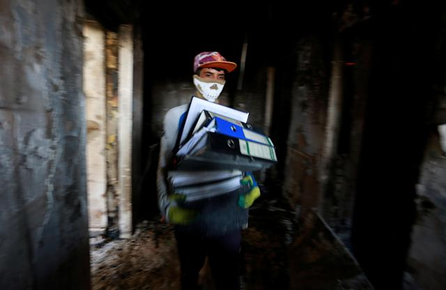 <p>A worker holds the remaining files from the fire of the municipality building of Basra, Iraq, Sept. 6, 2018. (Photo: Alaa al-Marjani/Reuters) </p>