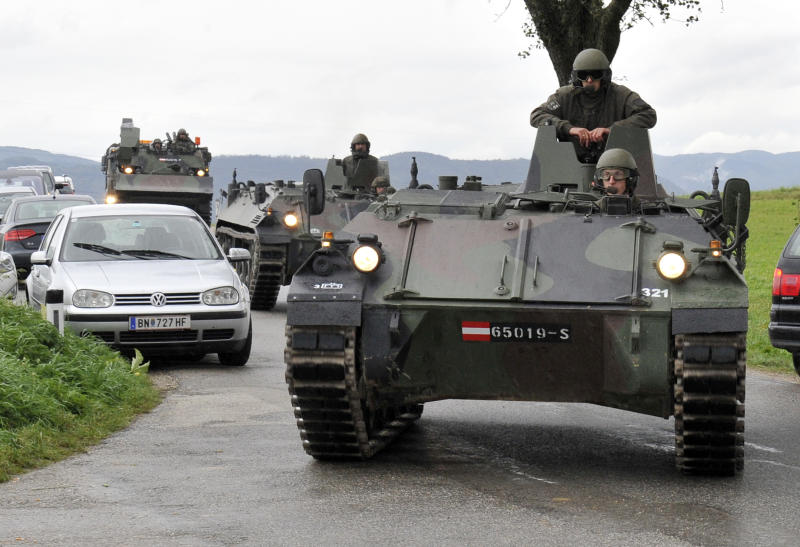 Austrian army soldiers in armored vehicles arrive near the villages of Grosspriel and Kollapriel some 90 kilometers (55 miles) west of Vienna, Austria, Tuesday, Sept. 17, 2013, where a man is barricading himself inside a farm building after he killed two police officers and the driver of an emergency rescue vehicle as the dpa news agency said, citing an unidentified police spokesman. Interior Minister spokesman Karl-Heinz Grundboeck said a third police officer was apparently being held by the shooter in the village of Kollapriel. He confirmed that three people were shot but refused to say whether their injuries were fatal, explaining that officials did not want to give the gunman information through news reports he was likely monitoring. (AP Photo/Hans Punz)