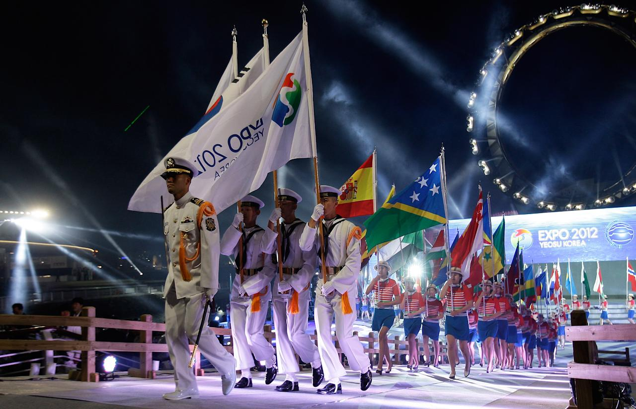 YEOSU, SOUTH KOREA - MAY 11:  Flag bearers hold national flags during the opening ceremony of the 2012 Yeosu Expo on May 11, 2012 in Yeosu, South Korea. More than 105 countries, 10 International Organizations and 10 million visitors are expected to participate in the expo that will open to the public on May 12 to August 12.  (Photo by Chung Sung-Jun/Getty Images)