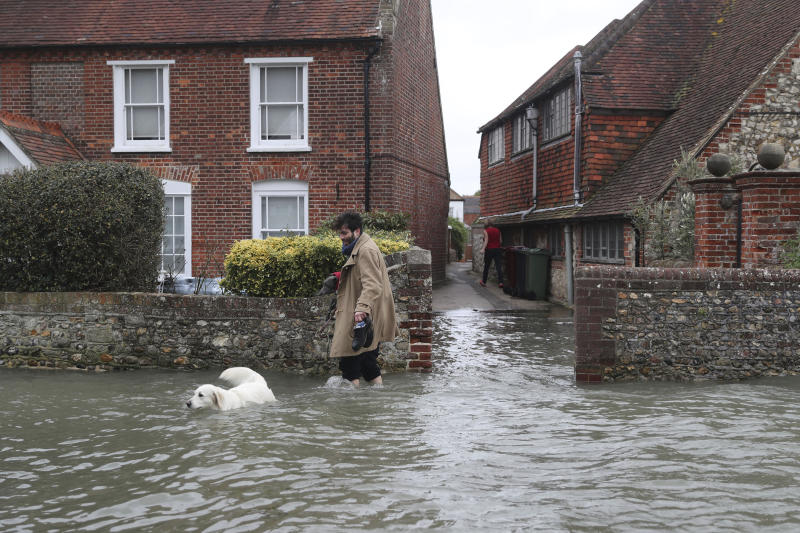 A man walks with a dog in flood water, in the aftermath of Storm Ciara, in Bosham, Sussex. (Steve Parsons/PA via AP)