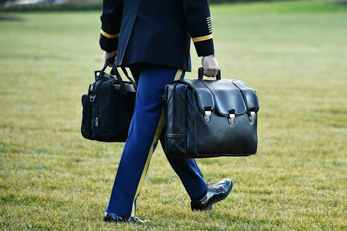 """<p>A military aide carries the nuclear """"football"""" with the equipment and nuclear codes to Marine One after the Trumps board. </p>"""