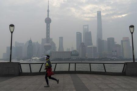 A jogger runs along the bund near the Huangpu river across the Pudong New Financial district, amid heavy smog in Shanghai