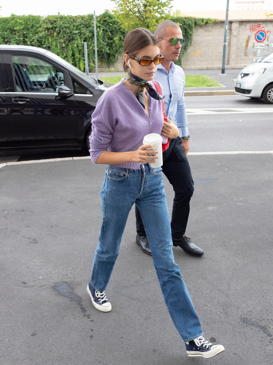 Back to sneakers, she elevated this cardigan look with rose-tinted sunnies and a tie around her neck.