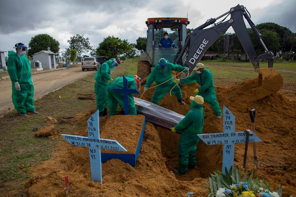 Gravediggers are helped by a backhoe to bury a COVID-19 victim at the Nossa Senhora Aparecida cemetery in Manaus, Amazonas state, Brazil, on January 13, 2021, amid the novel coronavirus pandemic. - In Manaus there is a shortage of hospital beds as cases increased at an alarming rate. The city, with two million inhabitants, had already experienced nightmarish scenes in April and May, with mass graves and refrigerated trucks parked in front of hospitals to pile up the dead. But the situation is even worse in the beginning of 2021, since between January 1 and 11, at least 1,979 people were admitted to hospitals due to the virus, against 2,128 for the whole month of April, the worst since the start of the pandemic. (Photo by MICHAEL DANTAS / AFP) (Photo by MICHAEL DANTAS/AFP via Getty Images)