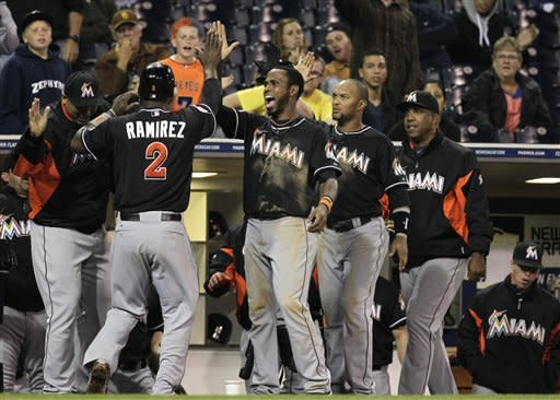 Miami Marlins' Hanley Ramirez, 2, is greeted at the dugout by teammates Jose Reyes, third from right, and Emilio Bonifacio, second from right, after scoring the winning run off a hit by teammate Omar Infante against the San Diego Padres in the twelfth inning during their baseball game Friday, May 4, 2012, in San Diego. (AP Photo/Gregory Bull)