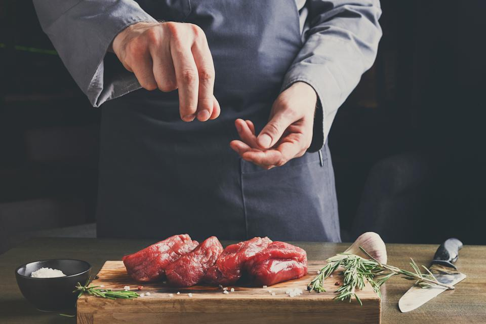 Man sprinkles filet mignon steaks with pepper salt. Chef working at open restaurant kitchen. Fresh meat, garlic and rosemary on wooden board. Modern restaurant cuisine backgroung
