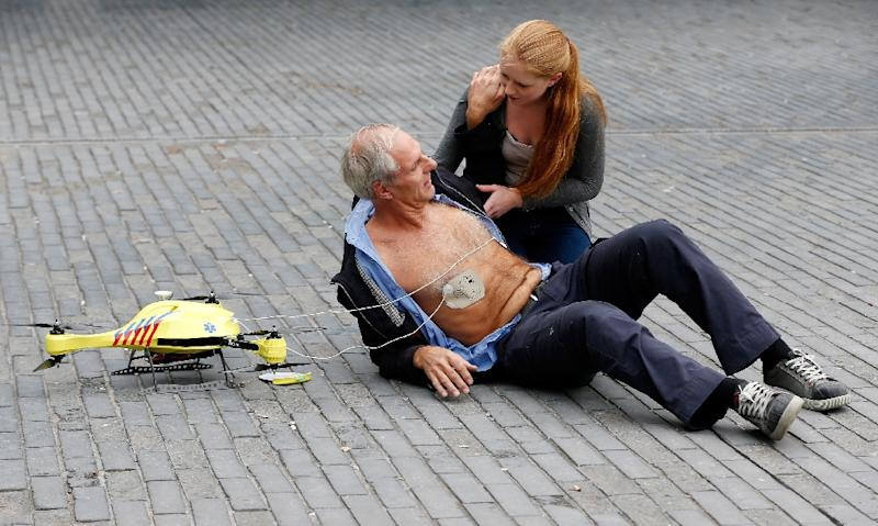 A woman gives a demonstration of an ambulance drone with built in defibrillator at the campus of the Delft Technical University in Delft on October 28, 2014. A Swedish report Tuesday said drones can drastically cut response times for delivering the life-saving equipment to victims. (AFP Photo/BAS CZERWINSKI)