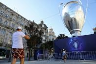 People take pictures in front of an inflatable model of the Champions League cup in Porto's central Aliados square as thousands of English fans make their way to Portugal's northern city for the League's final match and hotels and bars hope for a boost aft