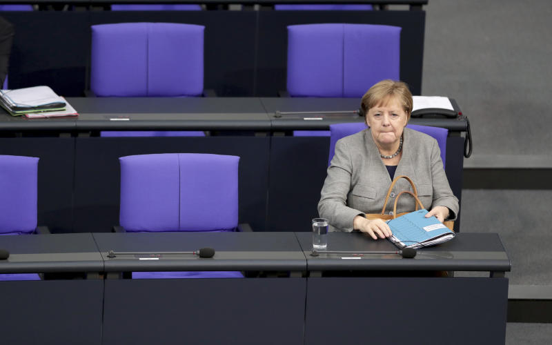 German Chancellor Angela Merkel arrives for a Q&A event as part of a meeting of the German parliament, Bundestag, at the Reichstag building in Berlin, Germany, Wednesday, Dec. 18, 2019. (AP Photo/Michael Sohn)