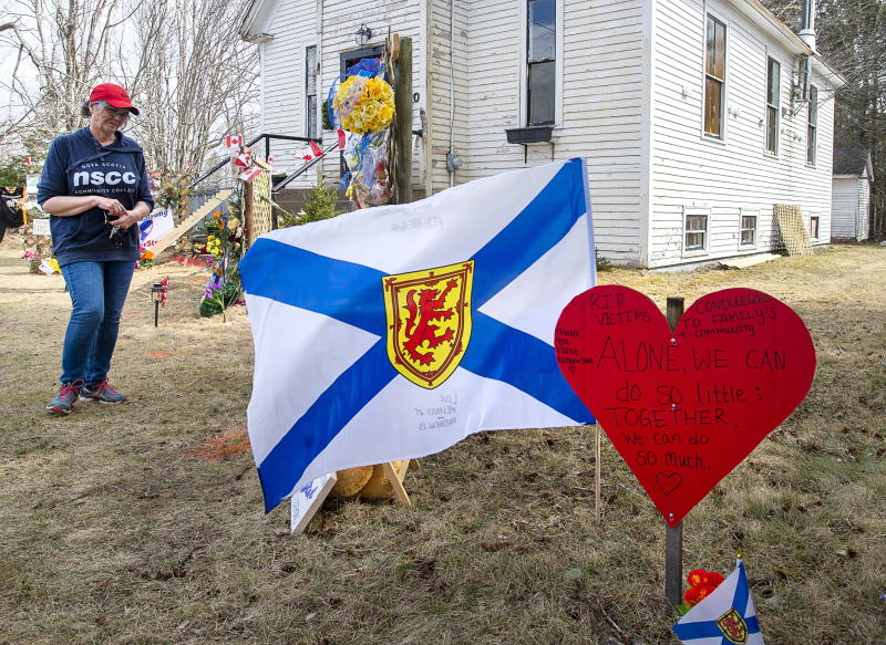 People pay their respects at a roadside memorial in Portapique, N.S. on Sunday, April 26, 2020. A man went on a murder rampage in Portapique and several other Nova Scotia communities killing 22 people. (Andrew Vaughan/The Canadian Press via AP)