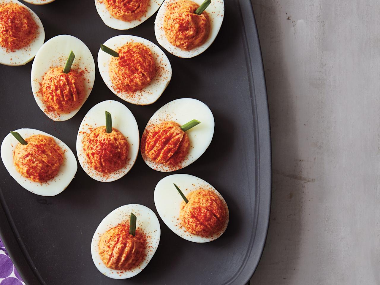 "<p>Serve these devilishly tasty treats as part of a Halloween feast. Roasted red peppers and paprika give the filling an orange hue reminiscent of jack-o-lanterns, while snipped chives resemble their stems. </p><p><a href=""https://www.myrecipes.com/recipe/red-pepper-deviled-eggs"">Roasted Red Pepper Deviled Eggs Recipe</a></p>"