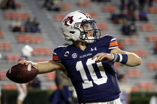 FILE- In this Saturday, Nov. 21, 2020, file photo, Auburn quarterback Bo Nix warms up for an NCAA college football game against Tennessee on in Auburn, Ala. Alabama quarterback Mac Jones and Auburn's Bo Nix have taken different paths to their starting jobs. Now, they'll lead their teams into the Iron Bowl for the second straight year. (AP Photo/Butch Dill, File)