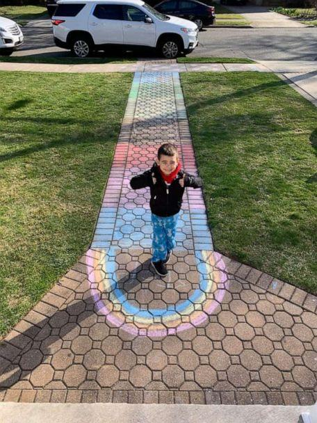 PHOTO: Rylan Nestro, 5, stands proud in front of a chalk rainbow he created to spread hope and joy in his Long Island, New York, community amid the coronavirus crisis. (Samantha Nestro)