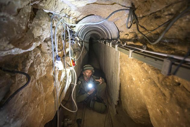 An Israeli army officer gives journalists a tour of a tunnel allegedly used by Palestinian militants for cross-border attacks, July 25, 2014. (AP/Jack Guez, Pool)